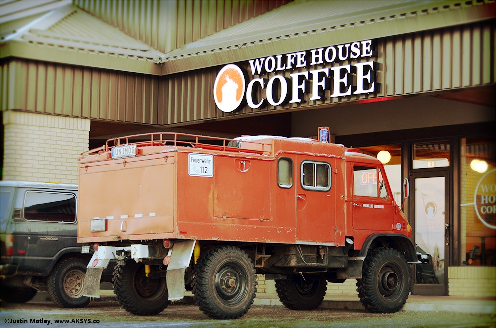 Unimog off-road adventure emergency vehicle and Toyota Land Cruiser FJ62 4x4 wagon at Wolfe House Coffee cafe in Anchorage, Alaska